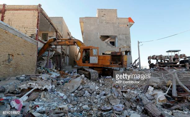 A picture taken on November 14 2017 shows an Iranian civil defence digger going through the debris of the buildings damaged by a 73magnitude...