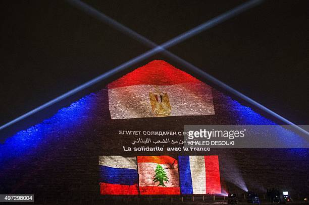 Picture taken on November 15, 2015 shows the great pyramid of Khufu illuminated with the French, Lebanese and Russian flags in Giza, outskirt of...