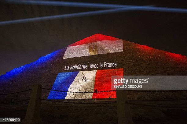 Picture taken on November 15, 2015 shows the great pyramid of Khufu illuminated with the French flag in Giza, outskirt of Cairo, during a ceremony in...