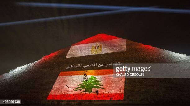 Picture taken on November 15, 2015 shows the great pyramid of Khufu illuminated with the Lebanese flag in Giza, outskirt of Cairo, during a ceremony...