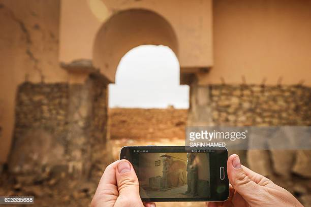 A picture taken on November 15 2016 shows a smartphone with a picture of the ancient ruins of Nimrud some 30 kilometres south of Mosul in the Nineveh...