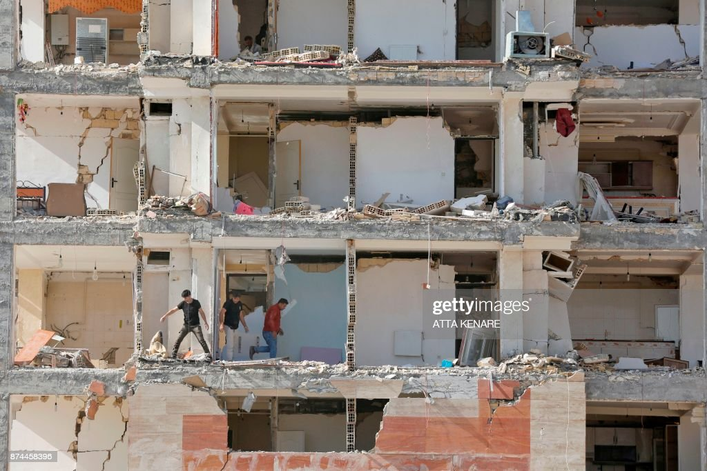 TOPSHOT - A picture taken on November 15, 2017 shows a view through the buildings left damaged by a 7.3-magnitude earthquake that struck days before in the town of Sarpol-e Zahab in Iran's western Kermanshah province near the border with Iraq, leaving hundreds killed and thousands homeless. /