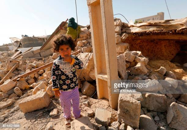 A picture taken on November 15 2017 shows an Iranian girl standing in the rubble of her home in Kouik village near to Sarpole Zahab two days after a...
