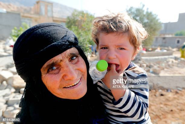 A picture taken on November 15 2017 shows an Iranian woman and child posing for a photo in Kouik village near to Sarpole Zahab two days after a...