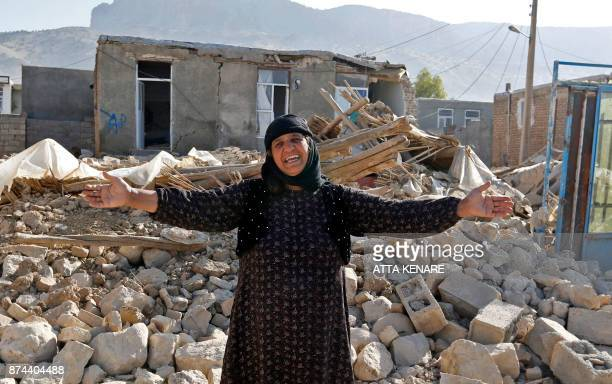 A picture taken on November 15 2017 shows an Iranian woman gesturing next to the rubble of her home in Kouik village near to Sarpole Zahab two days...