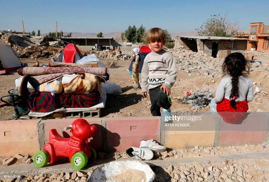 TOPSHOT - A picture taken on November 15, 2017 shows Iranians children next to the rubble of their home in Kouik village near to Sarpol-e Zahab, two days after a 7.3-magnitude earthquake struck Iran's western Kermanshah province near the border with Iraq, leaving hundreds killed and thousands homeless. Iranian authorities scramble to help tens of thousands of people left homeless by a major quake on the border with Iraq that killed more than 400 people as anger mounts among residents at what they see as a slow response. /