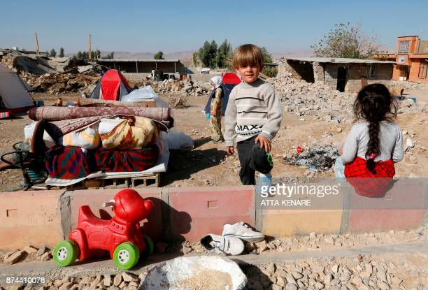TOPSHOT A picture taken on November 15 2017 shows Iranians children next to the rubble of their home in Kouik village near to Sarpole Zahab two days...