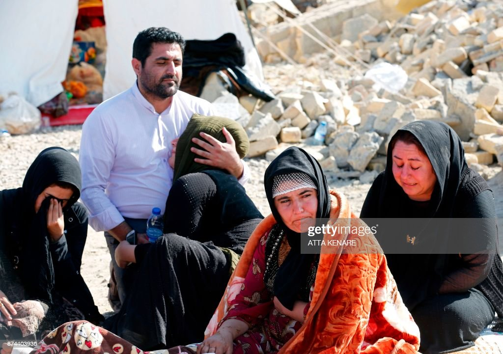 A picture taken on November 15, 2017 shows Iranians mourning next to the rubble of their home in Kouik village near to Sarpol-e Zahab, two days after a 7.3-magnitude earthquake struck Iran's western Kermanshah province near the border with Iraq, leaving hundreds killed and thousands homeless. Iranian authorities scramble to help tens of thousands of people left homeless by a major quake on the border with Iraq that killed more than 400 people as anger mounts among residents at what they see as a slow response. /