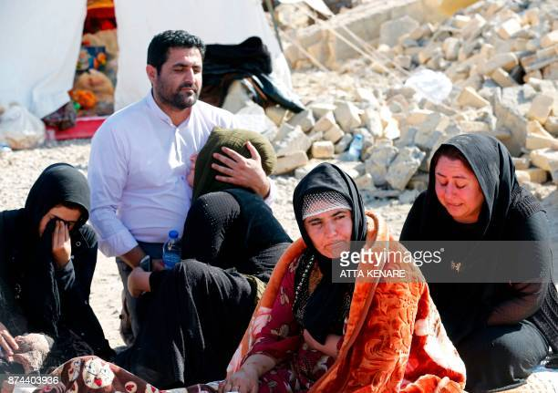 A picture taken on November 15 2017 shows Iranians mourning next to the rubble of their home in Kouik village near to Sarpole Zahab two days after a...