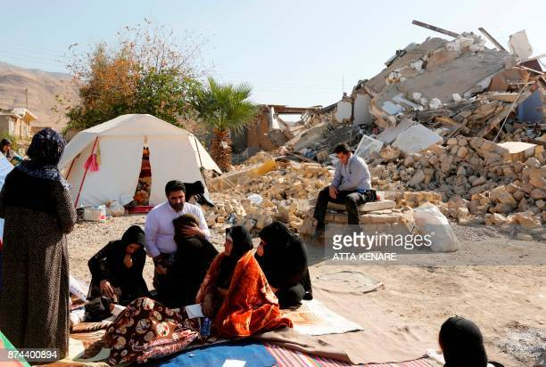 TOPSHOT A picture taken on November 15 2017 shows Iranians sitting next to the rubble of their homes two days after a 73magnitude earthquake struck...