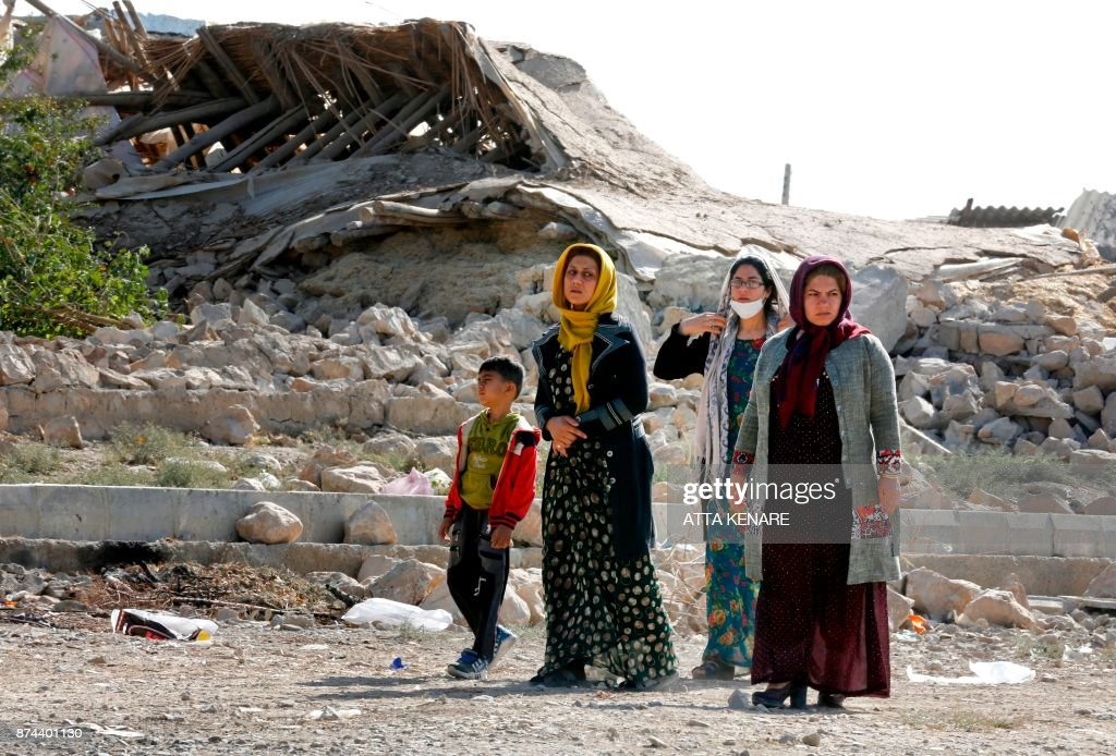 TOPSHOT - A picture taken on November 15, 2017 shows Iranians walking past the rubble of buildings in Kouik village near to Sarpol-e Zahab, two days after a 7.3-magnitude earthquake struck Iran's western Kermanshah province near the border with Iraq, leaving hundreds killed and thousands homeless. Iranian authorities scramble to help tens of thousands of people left homeless by a major quake on the border with Iraq that killed more than 400 people as anger mounts among residents at what they see as a slow response. /