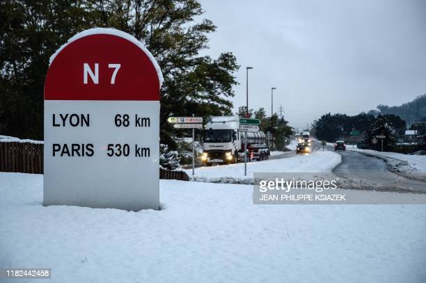 A picture taken on November 15 2019 near TournonsurRhone shows a road sign as road is covered with snow France's weather service placed 11...