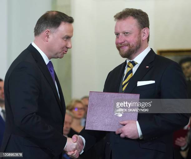 Picture taken on November 15, 2019 shows Polish Health Minister Lukasz Szumowski shaking hands with Polish President Andrzej Duda during the...