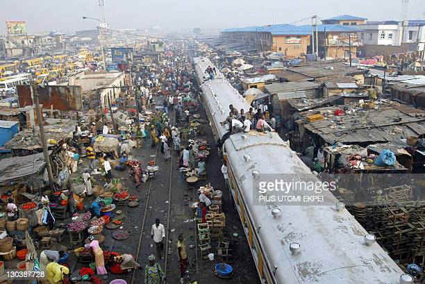 A picture taken on November 16 2007 shows commuters sitting ontop of a train chasing away vendors hawking their wares on the rail track at Oshodi...