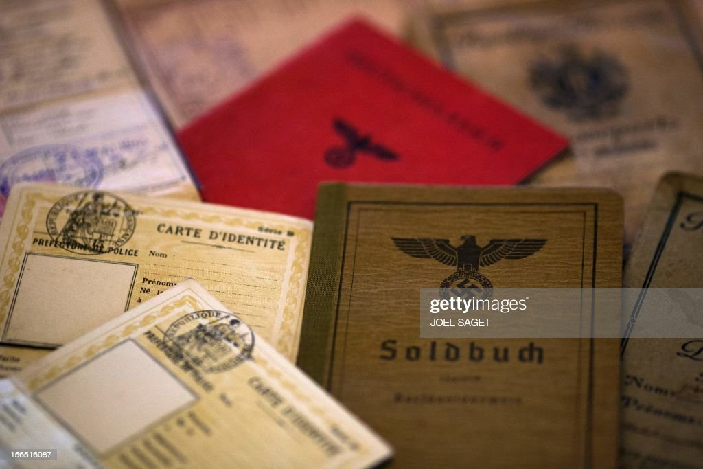 A picture taken on November 16, 2012 at Argentina's born and French photographer, Adolfo Kaminsky's home in Paris shows fake documents made during the WWII. Born in a Jewish family from Russia, Kaminsky is a former French Resistance, who forged identity documents for the National Liberation Front and French draft dodgers during the Algerian War.