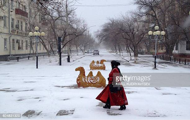 TOPSHOT A picture taken on November 16 2016 shows a woman walking along a street during a snowfall in Baikonur Kazakhstan Central Asia's Kazakhstan...