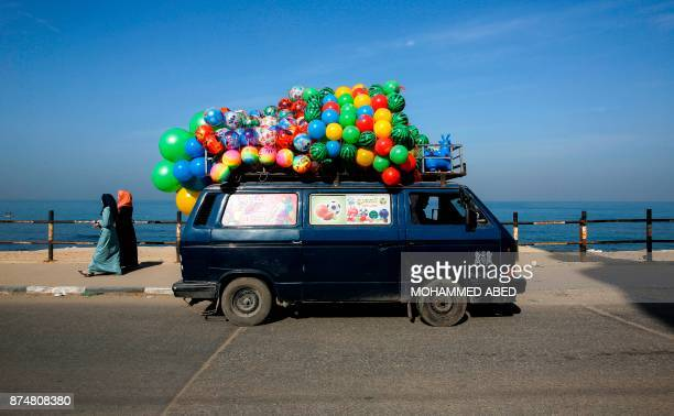 TOPSHOT A picture taken on November 16 2017 shows a minibus loaded with balloons driving along the coastal road by the beach in Gaza City / AFP PHOTO...