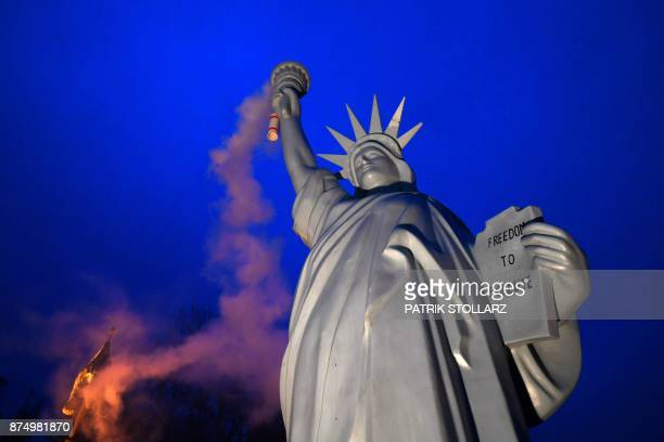 TOPSHOT A picture taken on November 16 2017 shows a replica of the Statue of Liberty emitting smoke from the torch created by Danish artist Jens...