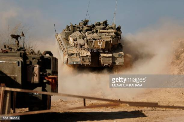 A picture taken on November 16 shows an Israeli soldier driving a tank at an army position overlooking southern Lebanon in the northern Israeli town...