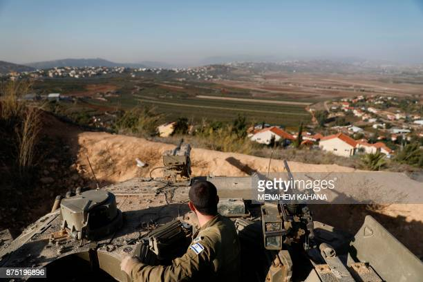 A picture taken on November 16 shows an Israeli soldier standing at attention in a tank at an army position in the northern Israeli border town of...