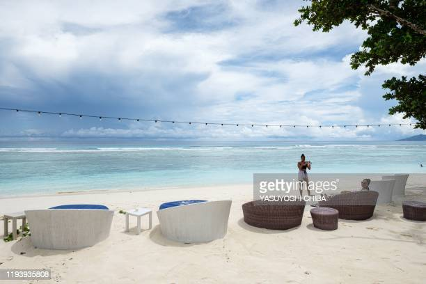 A picture taken on November 16 shows tourists taking pictures at the beach of Hilton Labriz only resort hotel located in Silhouette Island the third...
