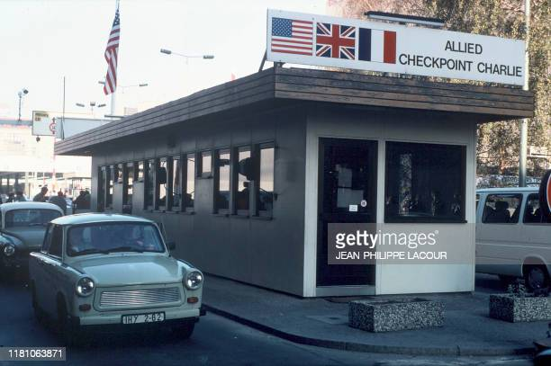 Picture taken on November 17, 1989 and made available on November 9, 2019 shows people in a Trabi car crossing the Allied Checkpoint Charlie crossing...