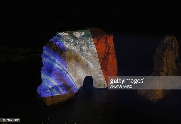 Picture taken on November 17, 2015 shows Beirut's landmark of Rawshe illuminated with the French national colours during a ceremony in tribute to the...