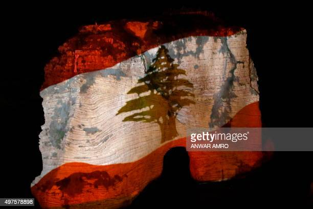 Picture taken on November 17, 2015 shows Beirut's landmark of Rawshe illuminated with the colours of the Lebanese flag during a ceremony in tribute...