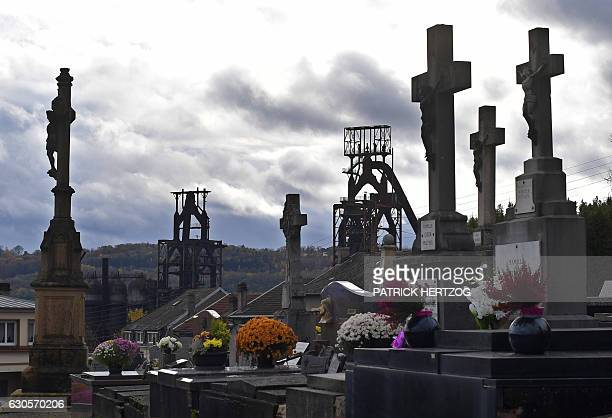 A picture taken on November 17 2016 shows a cemetery near the blast furnaces of the steel plant in Hayange eastern France / AFP / PATRICK HERTZOG