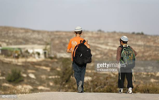A picture taken on November 17 2016 shows teenagers walking in a street of the settlement outpost of Amona which was established in 1997 in the...