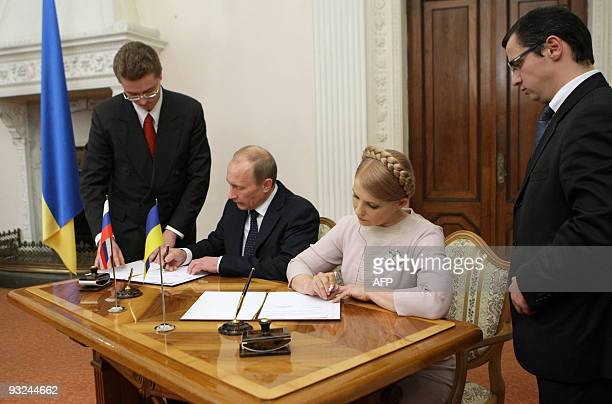 Picture taken on November 19 2009 shows Russian Prime Minister Vladimir Putin signing document with his Ukrainian counterpart Yulia Tymoshenko in...