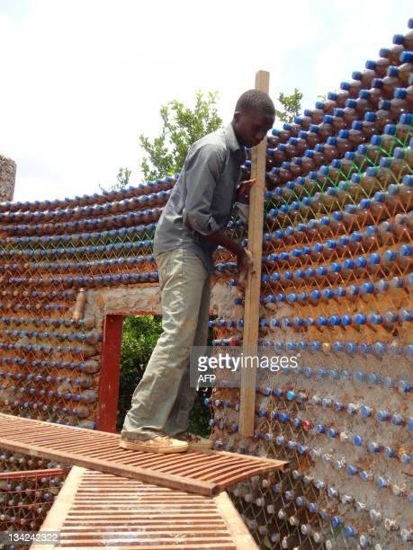 A picture taken on November 2 2011 shows nineteenyear old mason Yahaya Musa checking a wall of made of sandfilled plastic bottles on November 2 2011...