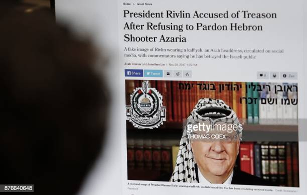 A picture taken on November 20 2017 shows a doctored image appearing on the Israeli news website Haaretz of President Reuven Rivlin wearing a...