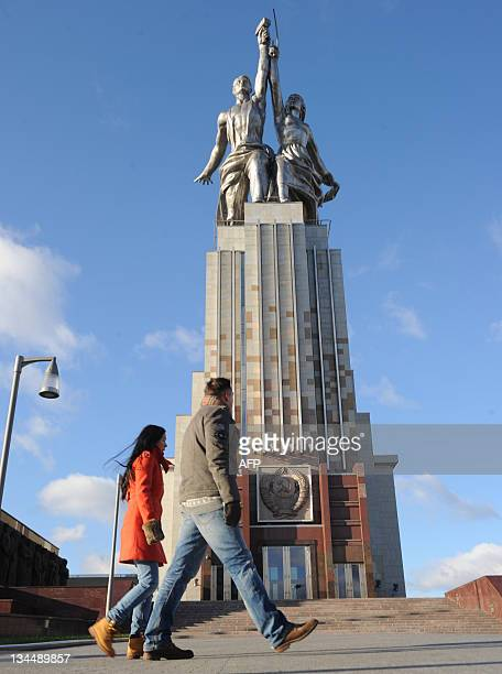 A picture taken on November 20 shows a couple walking past the 1937 Worker and Kolkhoz Woman 245 m high stainless steel sculpture by Vera Mukhina in...