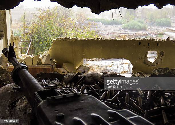 A picture taken on November 22 2016 shows a Russian DShK heavy machine gun lying over spent rounds in a position during Syrian forces' assault to...