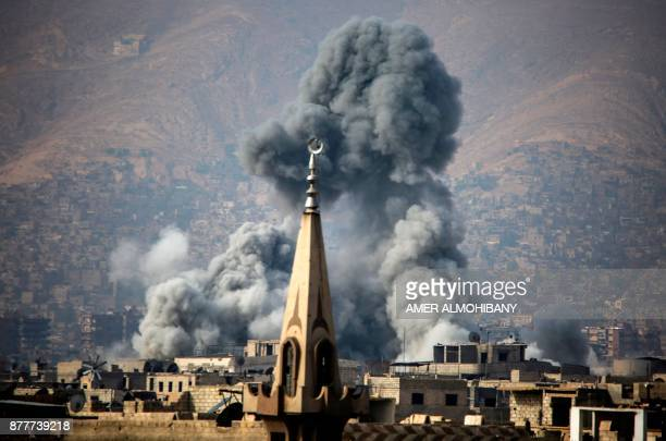 TOPSHOT A picture taken on November 23 2017 shows smoke rising following a reported air strike on the rebelheld besieged town of Arbin in the Eastern...