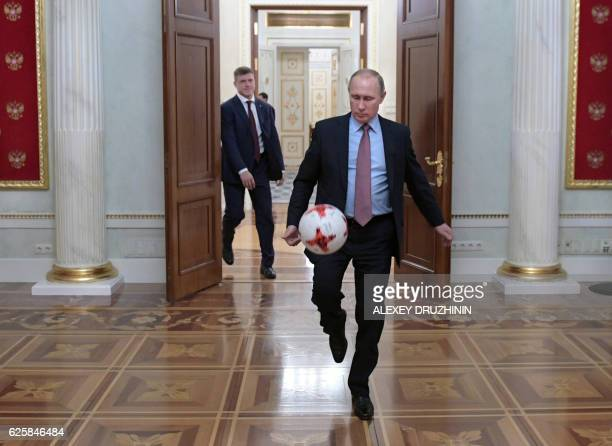 A picture taken on November 25 2016 shows Russian President Vladimir Putin playing with an official match ball for the 2017 FIFA Confederations Cup...