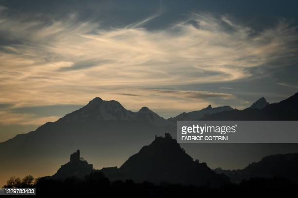 Picture taken on November 25 shows the Tourbillon Castle and the fortified church Valere Basilica overlooking the city of Sion at sunset in the Swiss...