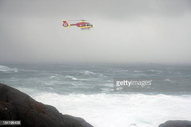 A picture taken on November 27 2011 shows a rescue helicopter searching for two people who ended up in the water at Stapnes outside Egersund in...