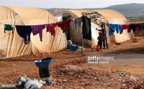 A picture taken on November 27 2017 shows clothes hung to dry on a washing line outside tents at the Furat camp for the displaced from Deir Ezzor...