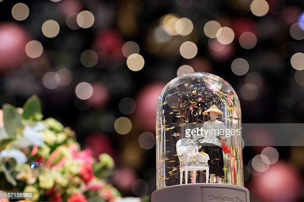 A picture taken on November 28 in Paris shows a snow globe with a Parisian woman designed by Christian Dior displayed at the Printemps department...