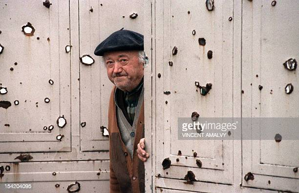 A picture taken on November 29 1991 shows a resident looking around as he stands at the bullet ridden door to this house in Vukovar Croatian Serb...