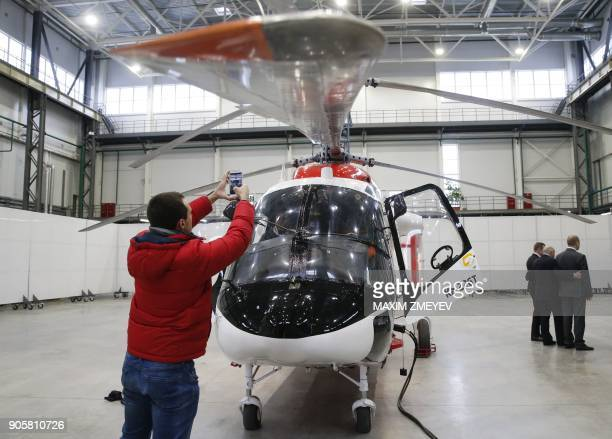 A picture taken on November 29 2017 shows a photographer taking pictures of a Russian utility helicopter Kamov Ka226 in a hangar of the Russian...