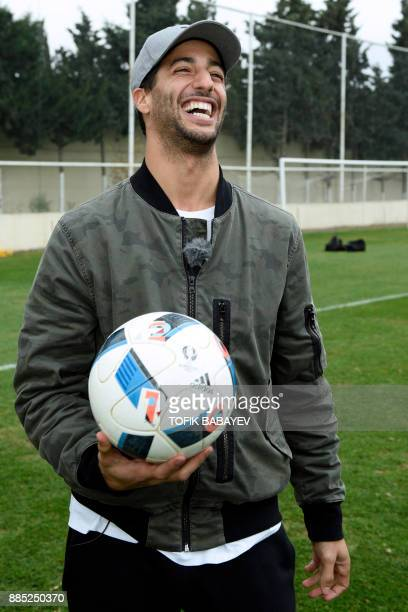 A picture taken on November 29 2017 shows Red Bull's Australian driver Daniel Ricciardo visiting the Qarabag FK training camp in Baku / AFP PHOTO /...