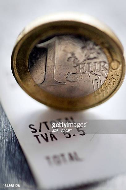 A picture taken on November 4 2011 at a restaurant in Paris shows a coin of one euro on an invoice indicating the 55 percent rate of the Valueadded...