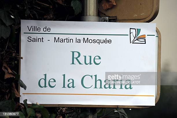 """Picture taken on November 4, 2011 in Saint-Martin-le-Vinoux, central France, shows a road sign that is covered up with a sticker to rename it """"Charia..."""