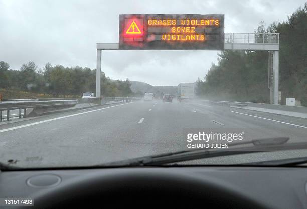 A picture taken on November 5 2011 from a car shows a roadsign warning of violent storms on the A8 highway near RoquebrunesurArgens Southern France...