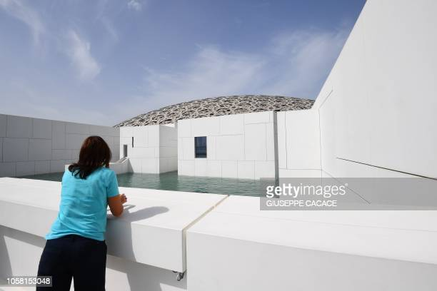 A picture taken on November 6 2018 shows a visitor at the Louvre Abu Dhabi museum in the Emirati capital The museum designed by the French architect...