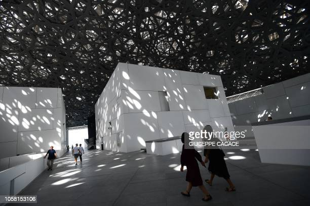 A picture taken on November 6 2018 shows visitors inside the Louvre Abu Dhabi museum in the Emirati capital The museum designed by the French...