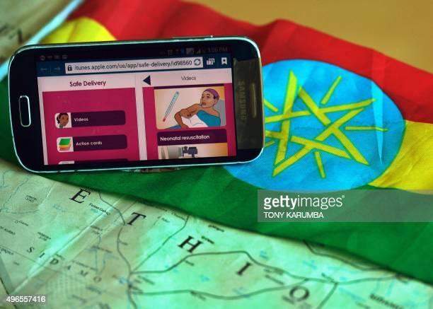 A picture taken on November 9 2015 in Nairobi shows a mobile phone application offering a simplified guide to childbirth in Ethiopia displayed on top...